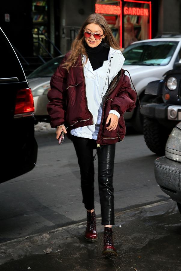 In a burgundy bomber jacket and boots with black leather pants and a light blue jumper.
