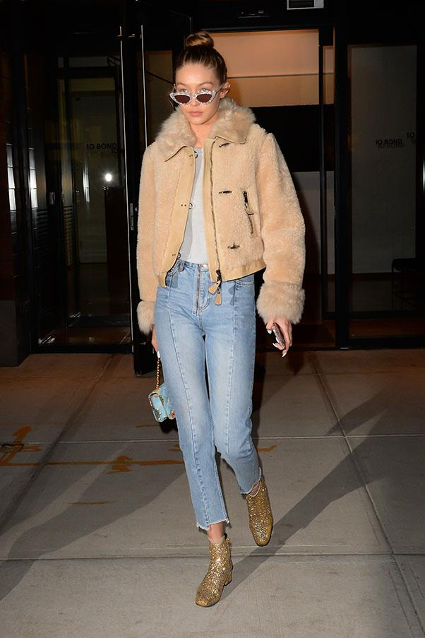 Gigi in blue jeans and gold sparkly shoes.