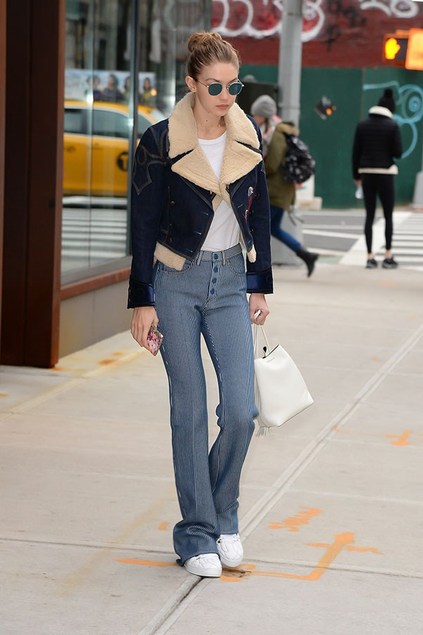 Gigi in striped trousers and a staple denim jacket.