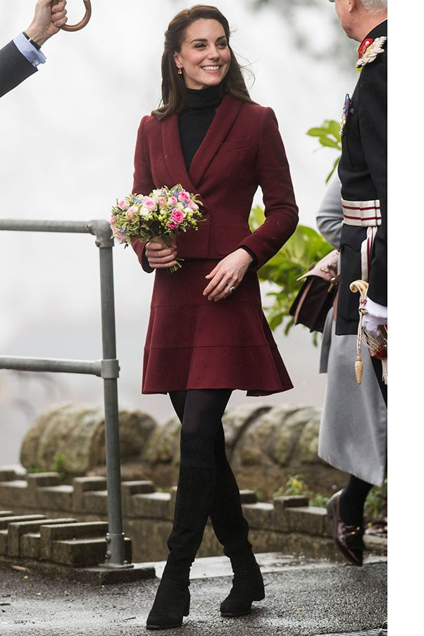 The Duchess wore a maroon skirt suit by Paule Ka and knee-high suede boots by Stuart Weitzman (the same boots favoured by Gigi Hadid and Kendall Jenner, may we add) to a royal event in Wales.