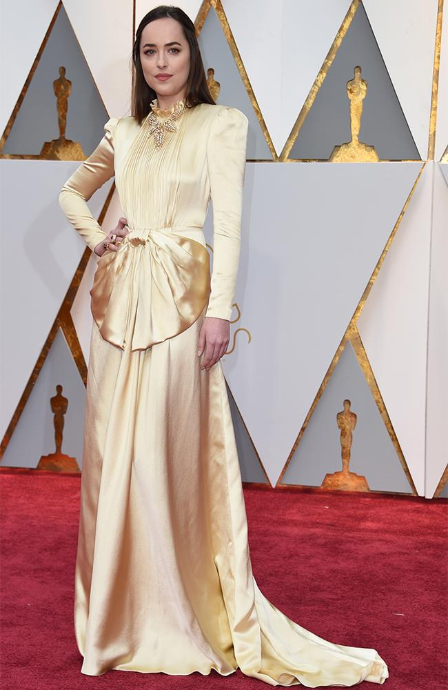 "<strong>Dakota Johnston: </strong> <br><br> ""I really like this dress—it has the DNA of a Gucci gown but a bit more pared down. The colour is magic and I love the neck and shoulder detail. It is very covered, but the dress fits her body so well."" — Caroline Tran, market editor <br><br> ""This dress is a strong statement. A disciplined and structured look without any frippery, and inevitably there will be goddess comparisons – but I think it's evidence that she's making choices about her image. Mission accomplished, I think."" — Eliza O'Hare, associate editor"