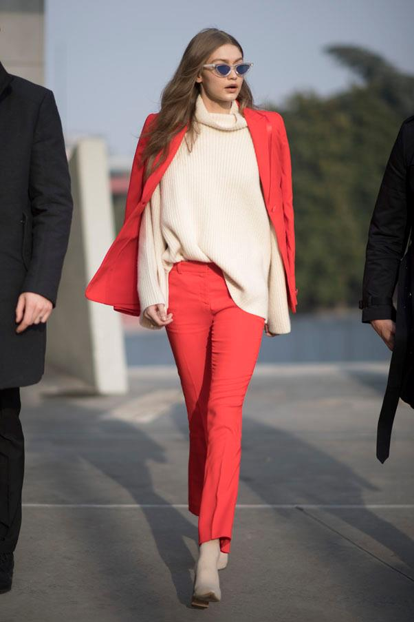 Hadid wearing a matching fiery red set with a beige knit, matching sock boots and her statement cat eye sunglasses.