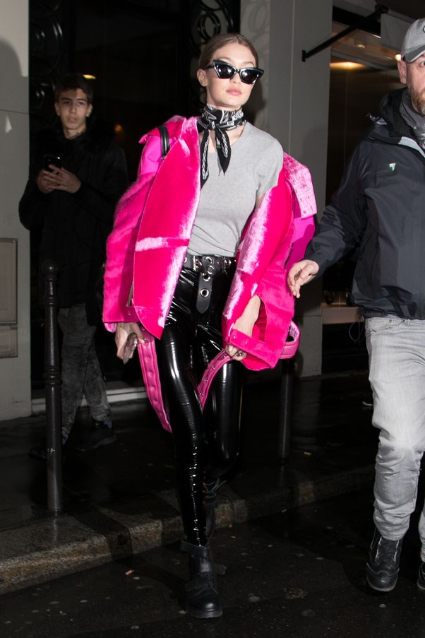 "Gigi stepped out in Paris during fashion week wearing a velvety hot pink coat, leather pants and a pair of sleek <a href=""https://www.karenwalker.com/collections/transformers/babou-black-sgkas1701551/blacksilver"">Karen Walker</a> shades."