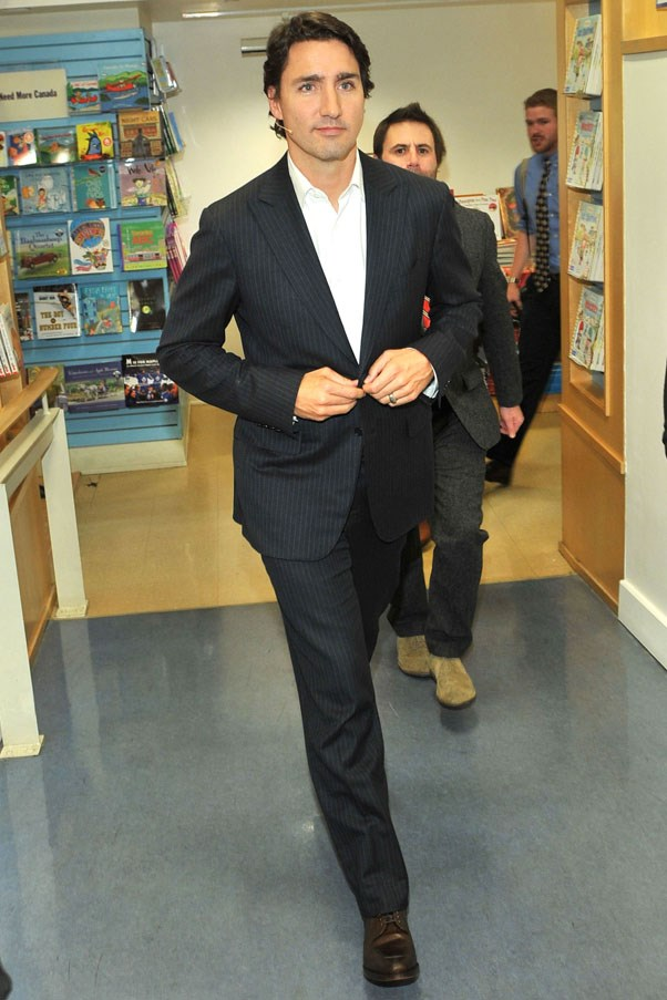 Buttoning his blazer and looking businesslike, 2014