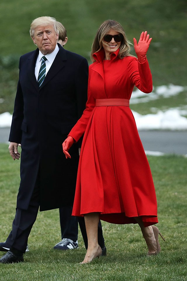 Melania wore an A-line, monotone fire engine red coat dress designed by Alice Roi, with matching gloves, Gucci shades and understated Gianvito Rossi pumps.