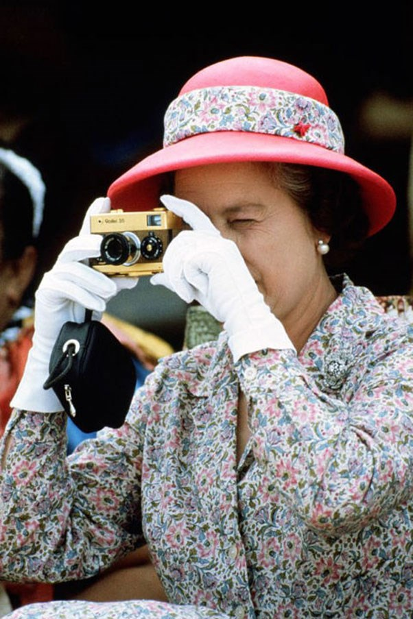 <strong>RED BOWLER</strong> <p><p> Queen Elizabeth snaps a photo in a bright red hat, wrapped with her dress's fabric, on a trip to Tuvalu in 1982.