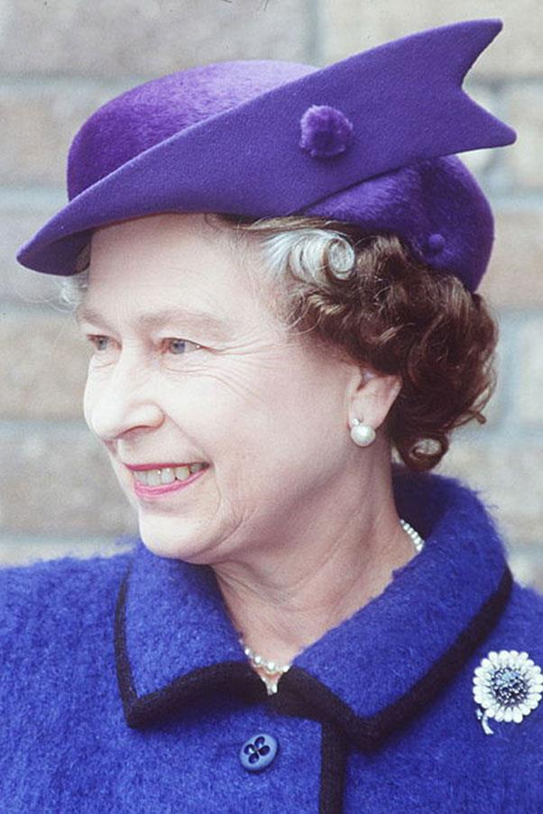 <strong>ROYAL PURPLE</strong> <p><p> The Queen wore a royal purple design by milliner Frederick Fox to contrast her black-trimmed blue coat in Swansea, Wales, 1989. Fox has a longtime history with queen and confessed that the queen rarely wears a hat more than 20 or 30 times — others, like those worn on special occasions, she'll wear just once. The hats that are selected for the Queen's travels, though, are truly the special ones — they travel in their own train car, if the Queen journeys by land.