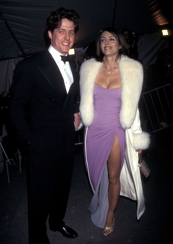 <strong>1997</strong> <br><br> When Elizabeth Hurley was 100% glam in a lilac thigh-slit gown and plush white fur.
