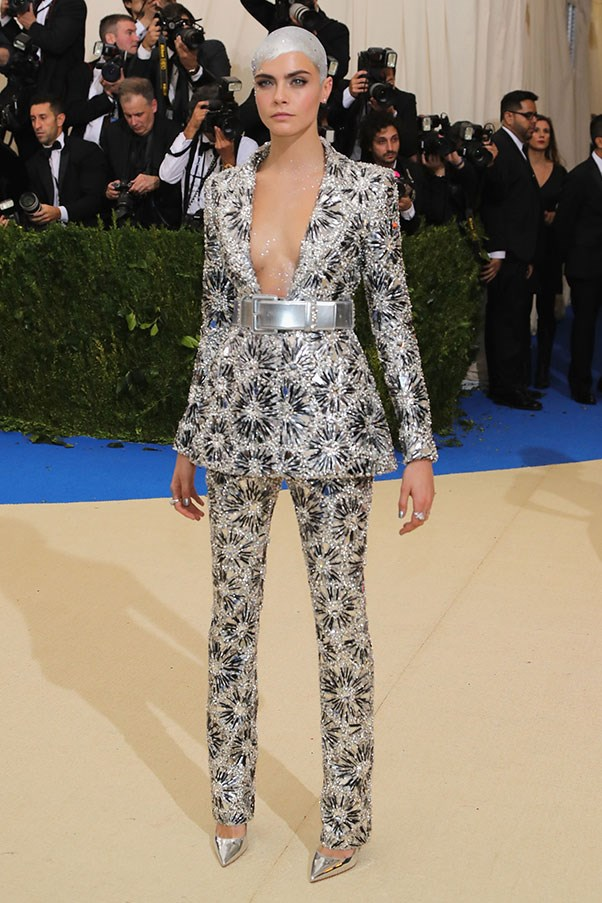 """<strong>Cara Delevingne in Chanel</strong><br><br> """"Only Cara could pull off a metallic suit and silver capped hair. This look was a great alternative to the sea of dresses and perfectly captured her unique aesthetic."""" - Kate Moffatt, digital weekend editor<br><br> """"Not sure what the connection is to this year's theme, but I love this sequinned suit situation on her. Bonus points for the spray-painted scalp."""" - Alison Izzo, digital managing editor"""
