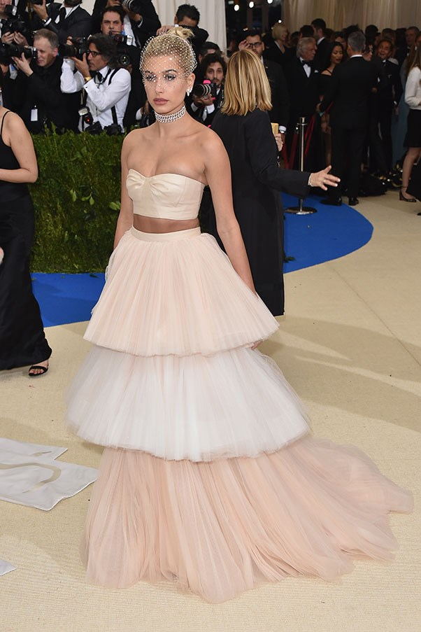 """<strong>Hailey Baldwin in Carolina Herrera</strong><br><br> """"Whether you like Hailey Baldwin or not you have to admit, this tiered blush Carolina Herrera number is absolutely divine. The best part? The minimalist ivory headpiece. Class in a glass."""" - Natasha Harding, digital fashion writer"""