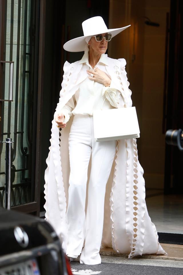 Celine stepped out in Paris wearing an all-white jumpsuit and matching cape by Ralph & Russo. A Celine bag topped off the look.