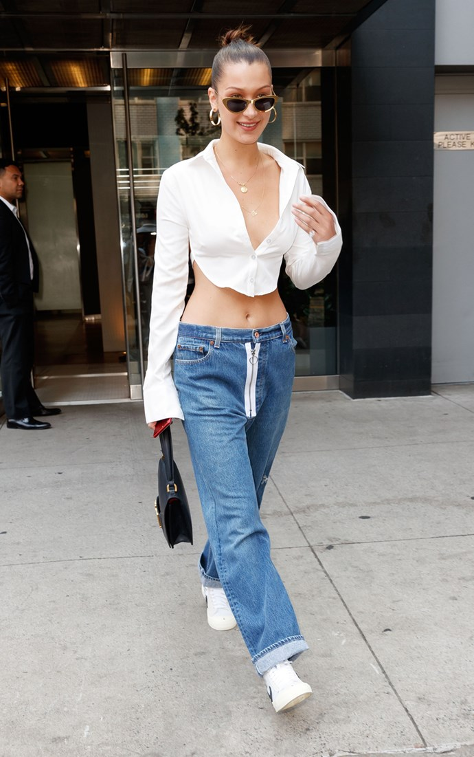 Bella stepped out in New York wearing a white button-down crop top with loose-fit jeans and a Dior handbag.