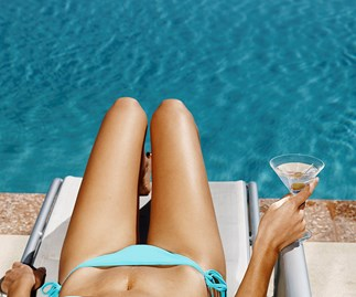 Woman drinking by the pool.
