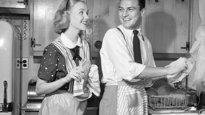 1950s husband and wife in the kitchen doing housework.
