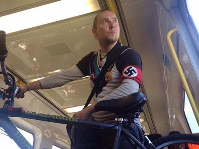 Real-life person wearing Nazi swastika outside of 1940s Germany