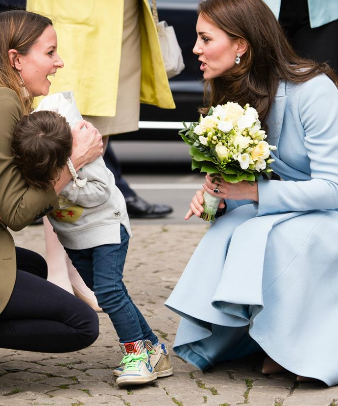 After graciously accepting the white and green posy, Kate went about consoling the little boy.