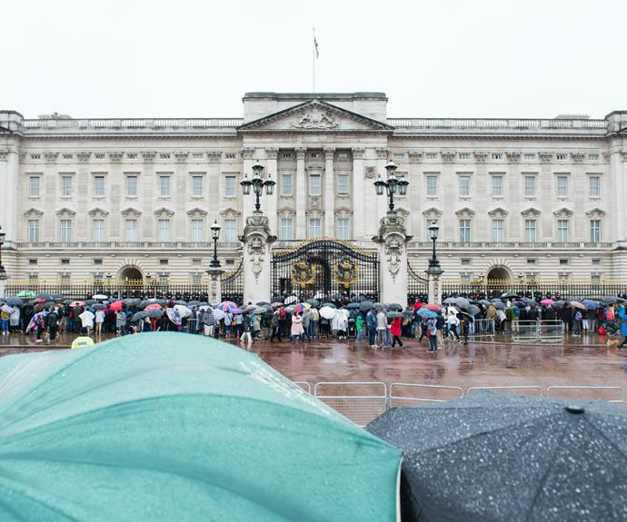 Despite the inclement weather, large crowds gathered at the palace gates for the significant moment in royal history.