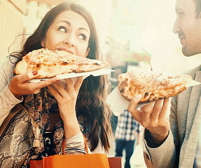 Couple indulging in pizza.