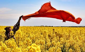 Woman feeling free in a grapeseed oil plantation