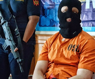 Why was Australia's latest accused drug smuggler forced to wear a balaclava and jumpsuit?