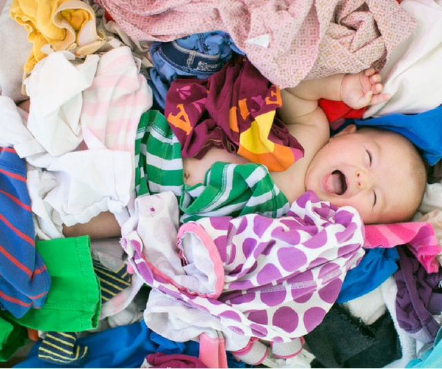 Laughing baby in pile of laundry