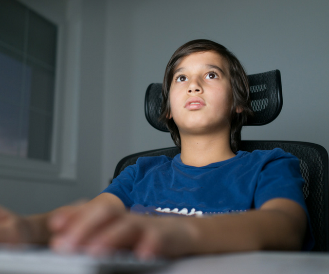 Young boy plays video game online