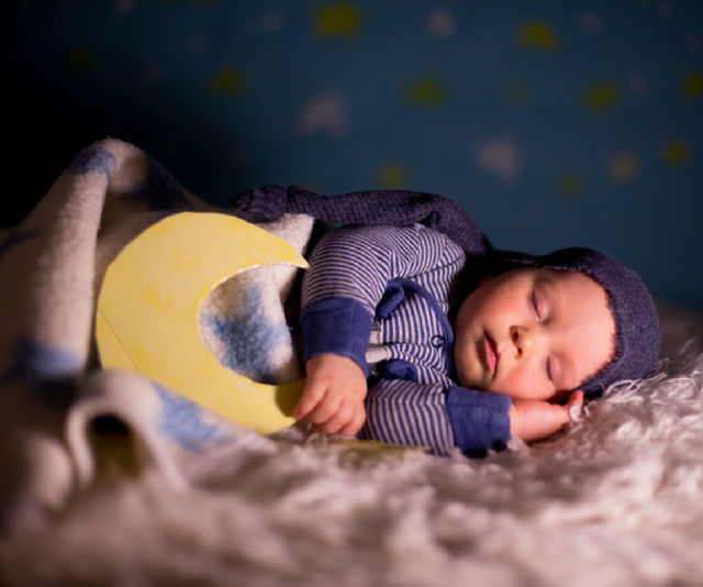 baby's star sign: Small baby sleeping while holding a cardboard cutout of a moon