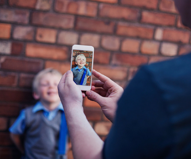 Parent takes a photo of child outside school