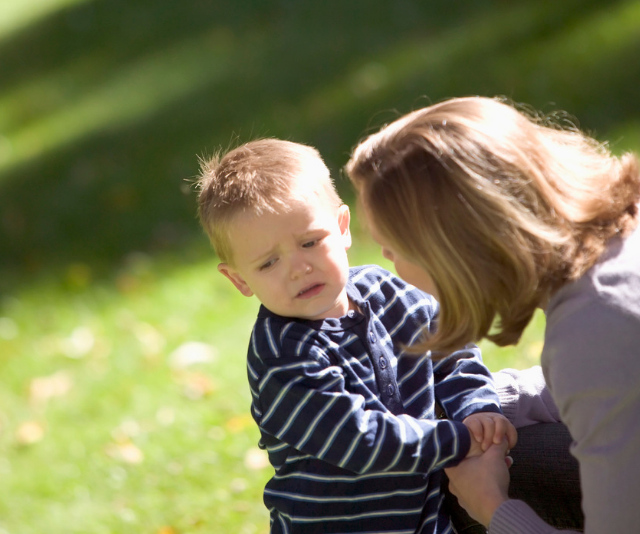 Mother trying to get toddler to listen at park