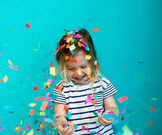 Small child throwing confetti against turquoise wall