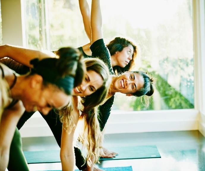 Four women practice yoga.
