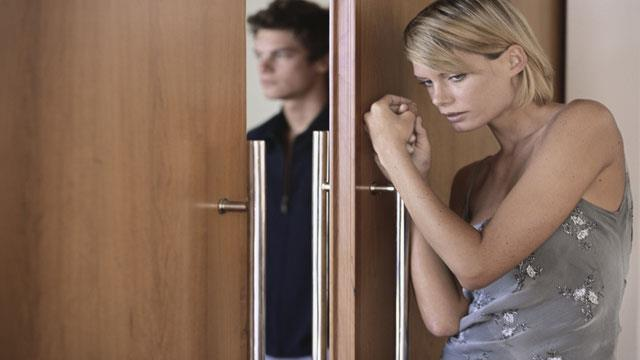 Woman scared and hiding from her partner's domestic abuse
