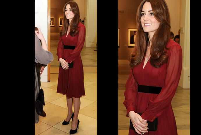 The duchess gracefully cradles her tiny bump.