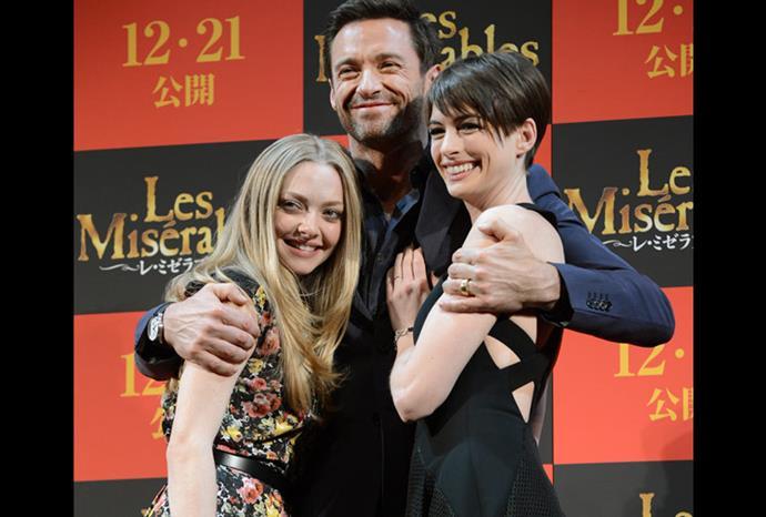 Anne cuddles up to co-stars Hugh Jackman and Amanda Seyfried.