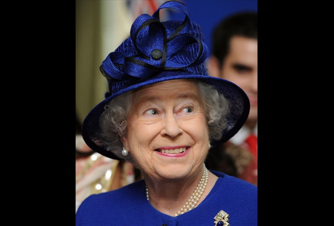 She is all smiles in this royal blue and black hat.