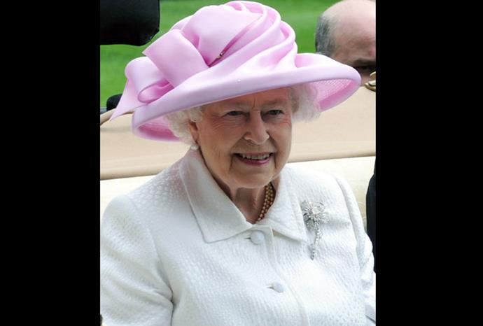 The Queen arrives in an open-top carriage in this simple pink hat.