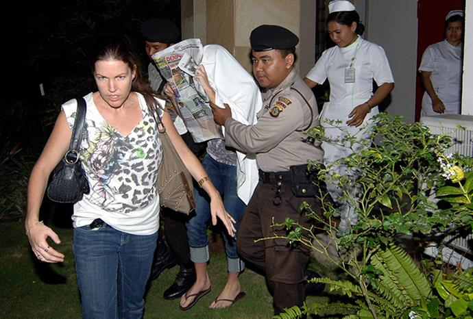 Schapelle hides under a newspaper after being released from hospital.