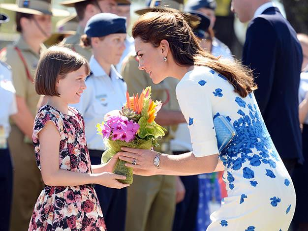 "The Duchess accepts a gift of flowers. As William reached out for a gift from one child he was told ""No! It's for Catherine!"" Photo: Getty Images"