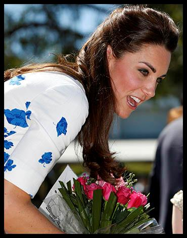 Kate accepts a bouquet of flowers from a little girl at the RAAF Base. Photo: Getty Images