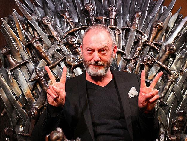 Showing off a lighter side, Liam Cunningham, aka Davos Seaworth throws some peace signs from the iron throne