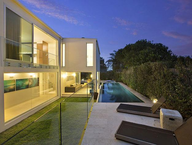 The exterior features a lap pool with sliding glass walls on all sides of the home to enjoy the view