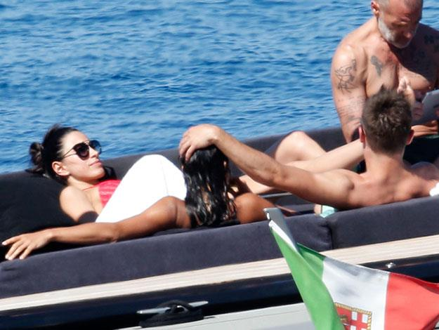 A view from behind as Zac affectionately strokes Michelle's hair while they chat with friends and soak up the sun.
