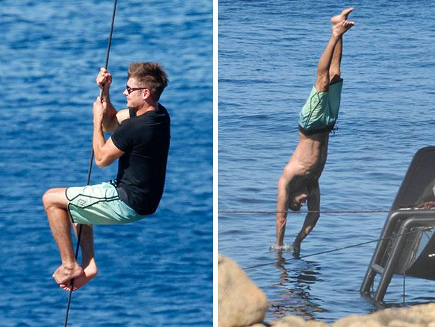 Zac Efron shows off his masculine moves as climbs ropes and dives into the cool water/