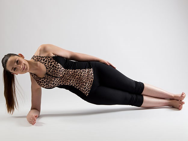 Side Plank  Areas targeted: Shoulders, triceps, back and obliques  Perform: Hold for 20-30 seconds each side  1. Start in a straight line with the body. Your feet will be flexed, legs stacked and propped up onto your forearm. Ensure that the elbow is directly underneath the shoulder.  2. Exhale to press up into a side plank position creating a straight line from the crown of the head to the feet. Hold this position, breathing throughout ensuring that the hips stay lifted.