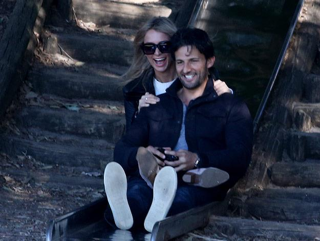 The lovebirds enjoy a slide down the slippery dip together and pose for a selfie on their way down.