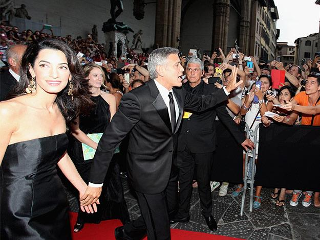 George holds Amal tight as he waves to the gathered crowd.