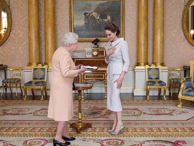 Angelina presented with the Insignia by the Queen.