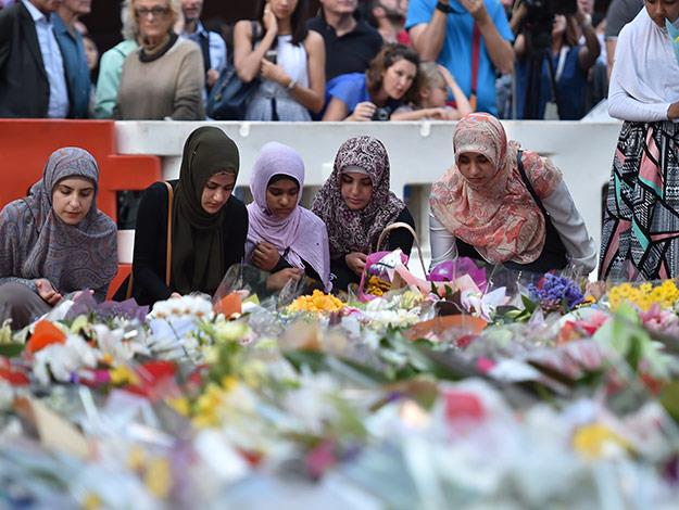 A group of women lay flowers at a makeshift memorial near the scene of a fatal siege in the heart of Sydney's financial district.
