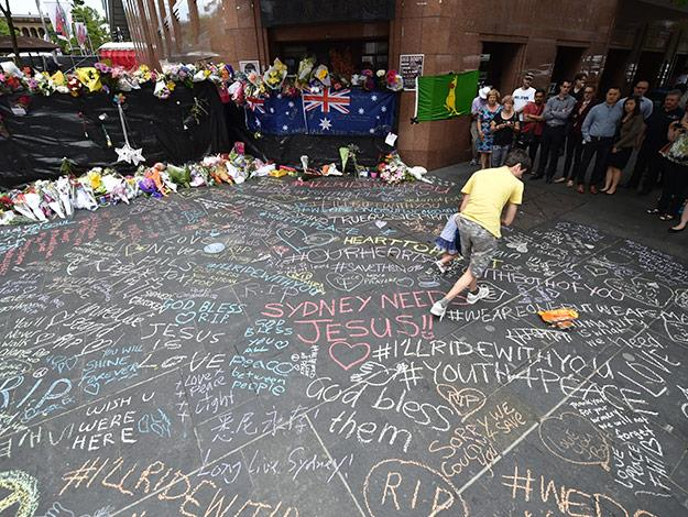 Visitors look at messages written on the ground at the barrier to the crime scene which has been turned into a makeshift memorial after the fatal siege.