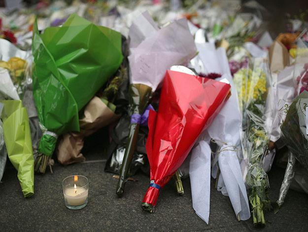 A lone candle burns surrounded by thousands of floral tributes.